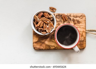 Pecan nuts in a bowl and hot coffee, top view