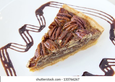 Pecan Nuts Pie with Slice with Dark Chocolate Drizzle on White Plate Closeup
