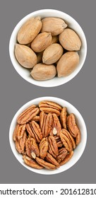 Pecan nuts, shelled and unshelled, in white bowls, over gray. Whole pecans and pecan halves, seeds and nuts of Carya illinoinensis, a popular snack. Close-up, from above, isolated, macro food photo.