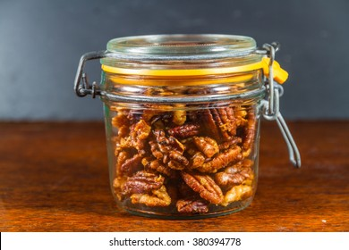 Pecan nuts and walnuts roasted with garlic and rosemary in jar. Dark background.