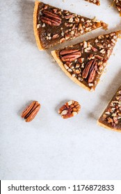Pecan Pie, made from butter enriched pastry with golden syrup, maple sauce and breadcrumbs, topped with pecans on grey background