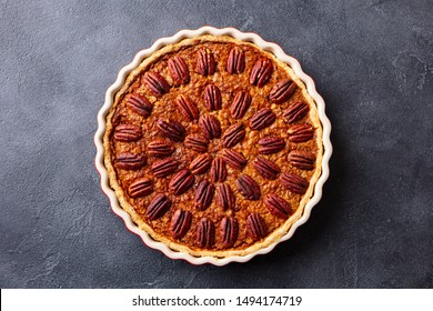 Pecan pie, tart in baking dish. Traditional festive Thanksgiving dessert. Dark background. Copy space. Top view.