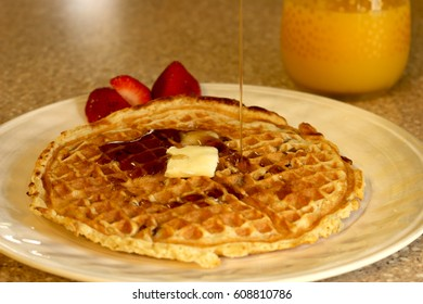 pecan waffle with butter, syrup and strawberries