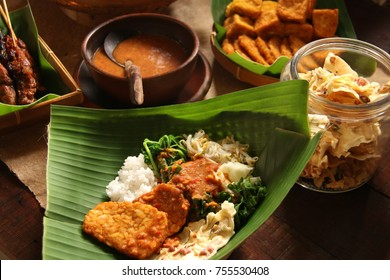 Pecel. Javanese traditional vegetable salad with sweet and spicy peanut dressing; served with steamed rice, fried tempeh, and peanut crackers on traditional banana leaf bowl called pincuk.