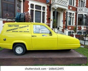 Peckham London UK 4/04/2018 A yellow three wheel Robin Reliant replica of The Only Fools and Horses Tv series, Trotters Independent Trading Co vehicle outside a guest house in Peckham South London.