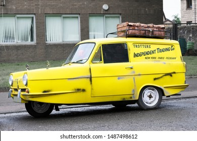 Peckham, London / UK - August 18th 2019: Vintage robin reliant yellow three wheeled car on council estate replica of only fools and horses TV programme vehicle