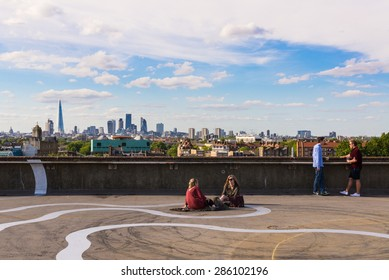 Peckham, London, UK - June 06 2015: Two girls and two guys drinking beer on the floor of a rooftop bar cafe in south-east London.View of the City of London skyscrapers and the Shard in the background.