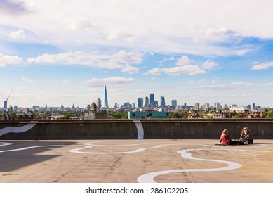 Peckham, London, UK - June 06 2015: Two girls sit on the floor of a rooftop bar cafe in south-east London.View of the City of London skyscrapers and the Shard in the background.