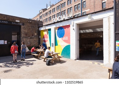 PECKHAM, UK - MAY 19, 2018: People drinking outside the Social bar in South London. Others are about to enter the Copeland Gallery.