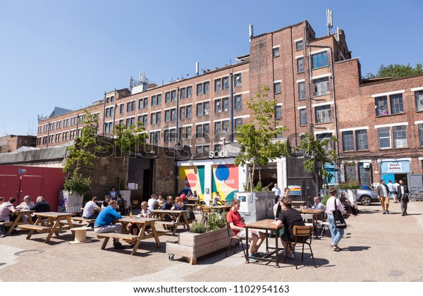 PECKHAM, UK - MAY 19, 2018: People drinking and hanging around outside a bar in the trendy Copeland Park in South London. The Bussey Building is in the background.