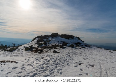 Pecny hill with quartzite rock formation, snow and hills on the background in Jeseniky mountains in Czech republic during winter day with blue sky and clouds