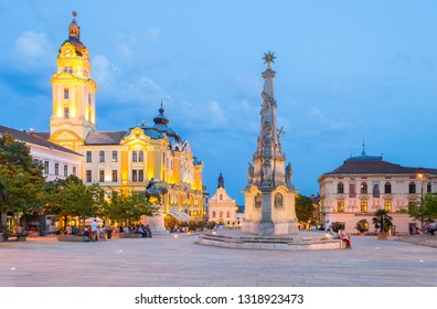 PECS, HUNGARY - APRIL 29, 2018: Evening view on the Town Hall, the Holy Trinity Statue, Saint Sebastian's Church and the Main Square (Szechenyi Square) filled with people