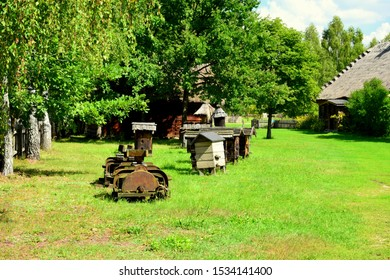 A peculiar collection of village items and equipment, including ploughing machine, several birdhouses and bee hives and others standing next to a lush orchard and an old cottage house in the distance