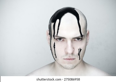 A peculiar young man with white skin bald hair and black paint on his head