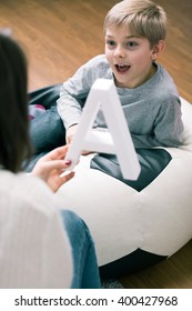 Pedagogue helping little boy to learn new letters. Woman holding big letter a and happy boy next to her