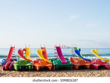 Pedakl boats on Benidorm resort beach with its landmark island in the background, Costa Blanca, Spain