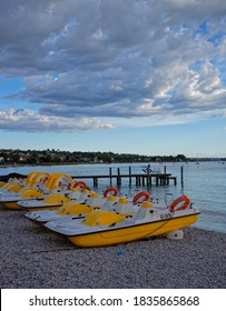 Pedal Boats on the Beach under a Cloudy Sky