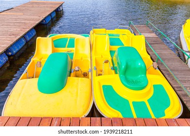 Pedal boats or paddle boats catamarans station. Yellow water bicycles locked at lake marina dock pier on sunny summer day. Summer leisure activity outdoors