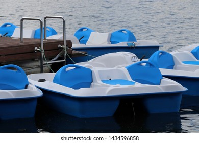 Pedal boats parked in a row on pond