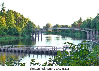 Pedestraiins bridge over the river surrounded by green trees in the evening sun light in Latvia Ogre city.