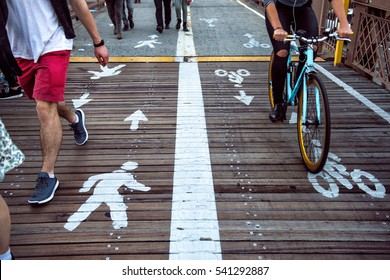 Pedestrian and bicycle riders sharing the street lanes with road marking in the city. People walking and riding on bicycle on city street.