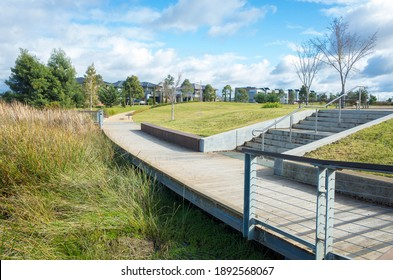Pedestrian boardwalk footpath in a suburban park leads to a neighborhood with some modern Australian houses in the distance. Concept of the public green land in the suburb and the local park.