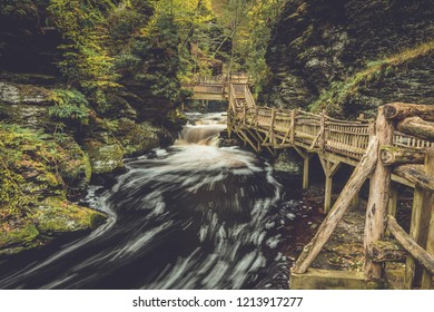 Pedestrian bridge curves around the gorges of Bushkill Falls in Poconos, PA, surrounded by lush fall foliage
