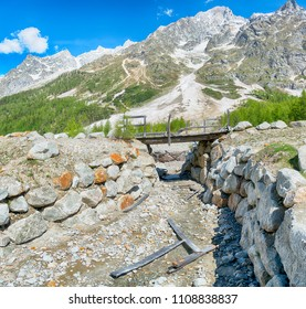 pedestrian bridge destroyed by an avalanche in winter, landscape in Ferret valley with mountains Grandes Jorasses in background