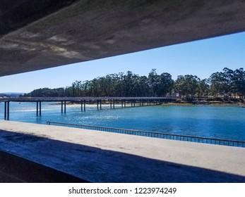 Pedestrian bridge on Vilanova de Arousa estuary framed by a building