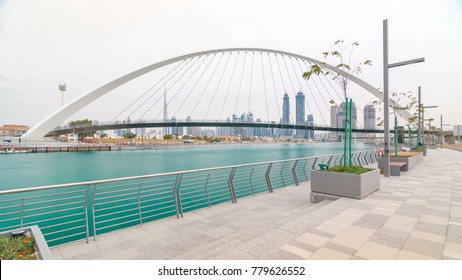 Pedestrian Bridge over the Dubai Water Canal cloudy day timelapse which links Dubai Creek to Jumeirah Beach weaving through Deira, Downtown Dubai and Safa Park. Skyscrapers skyline. Dubai, United Arab
