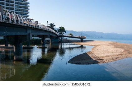 Pedestrian bridge over rio cuale in Puerto Vallarta, Mexico. Nice reflection in the water. Sunny and clear blue sky.