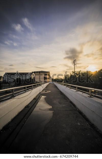 a pedestrian bridge with sunset