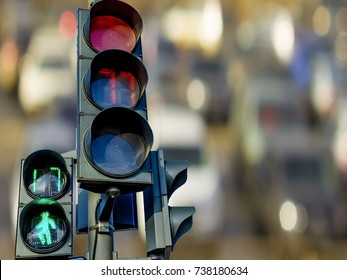 Pedestrian and car traffic lights with a timer on the background of cars on the road.