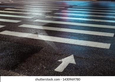 pedestrian crossing at night in the blue light. pedestrian lanes on wet asphalt in neon lights.