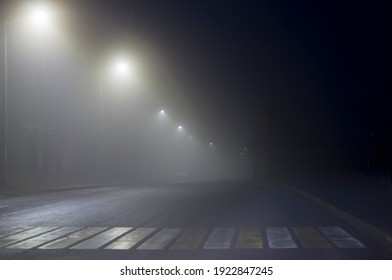 Pedestrian crossing at night in the fog, lighting lanterns go into the distance at night in the fog