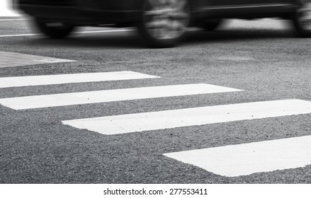 Pedestrian crossing road marking and fast moving car, photo with selective focus and shallow DOF