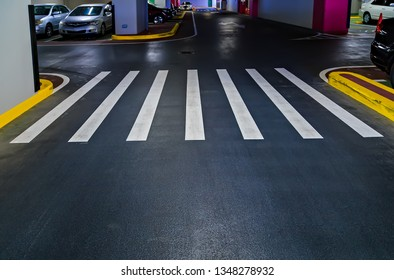 Pedestrian crossing with road white marking lines on asphalt underground garage or parking car park