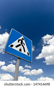 Pedestrian crossing sign against a blue cloudy sky.Crosswalk into paradise concept shot.
