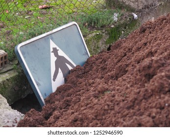 Pedestrian crossing sign buried in mound of earth in Andalusian village