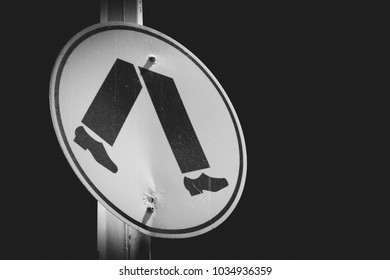 A pedestrian crossing sign taken at night in black and white.