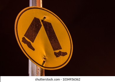 A pedestrian crossing sign taken at night.