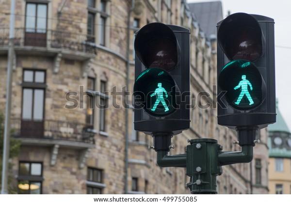 Pedestrian crossing traffic lights show green signal to go
