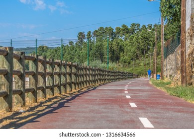 Pedestrian and cycle eco path, with a barrier of wooden trunks, man walking and vegetation and sky as background, in Viseu, Portugal