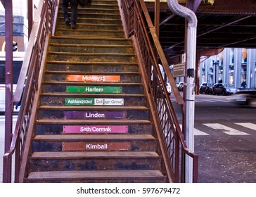 """Pedestrian from knees down, seen with briefcase walking up steps leading to a Chicago Elevated """"El"""" Train on bustling city corner of Adams and Wabash."""