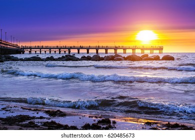 Pedestrian pier extends into the sea. Sunset at Baltic sea in resort Palanga, Lithuania. Rays of sun shine through the low cirrus clouds. Tidal waves wash the sandy beach in cloudy weather