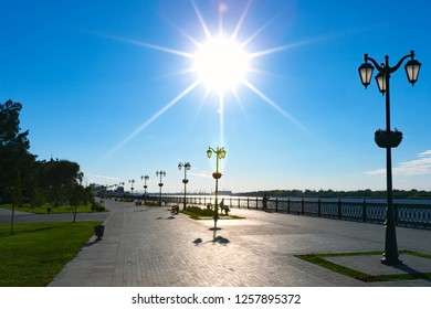 Pedestrian promenade on the banks of the Volga River in bright sunshine, wide pavement walkway from paving slabs and picturesque view of the city. Petrovskaya embankment, Astrakhan, Russia.
