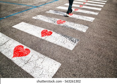 Pedestrian road crossing with illustrated red heart symbols on the floor. Conceptual man in love on the walk.