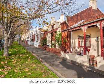 Pedestrian sidewalk and Victorian style houses in a quiet neighbourhood street. View of a Melbourne's old residential suburb. North Melbourne, VIC Australia.