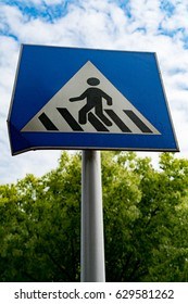 pedestrian sign or crosswalk sign with blue sky and green tree