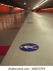 pedestrian sign on the floor of a parking garage